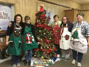Employees & Volunteers show off their holiday inspired aprons!