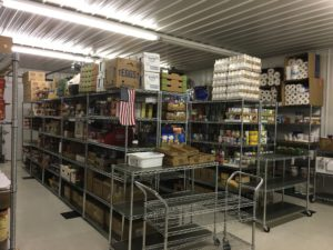 Stainless steel shelving holds the dry and canned goods. Rolling carts help to bring the food to the front for selection.
